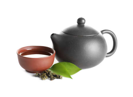 Teapot near cup of Tie Guan Yin oolong and leaves on white background 写真素材