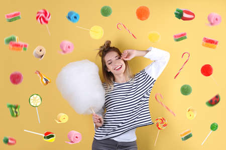 Young woman with cotton candy and flying sweets on color background 版權商用圖片