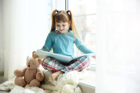 Cute little girl with teddy bear sitting near window and reading book at home