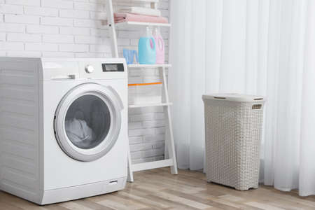 Modern washing machine near brick wall in laundry room interior