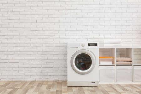 Lavatrice moderna vicino al muro di mattoni nell'interno della lavanderia, spazio per il testo
