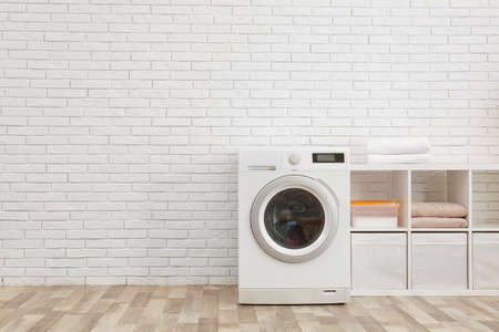 Machine à laver moderne près du mur de briques à l'intérieur de la buanderie, espace pour le texte