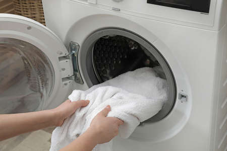 Woman taking clean towel from washing machine in laundry room, closeup