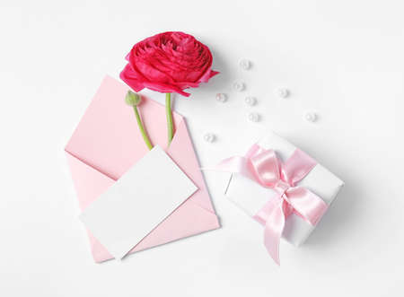 Composition with beautiful ranunculus flower and card on white background, top view. Space for text