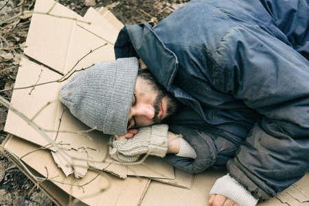 Poor homeless man lying on cardboard outdoors