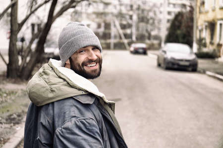 Poor homeless man standing on city street