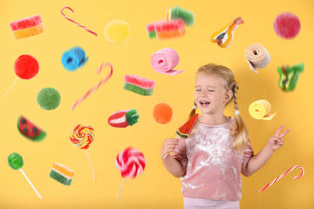 Adorable little girl with lollypop and flying candies on color background Stock Photo
