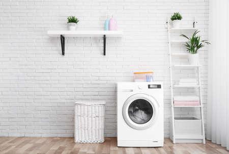 Lavadora moderna cerca de la pared de ladrillo en el interior de la sala de lavandería, espacio para texto