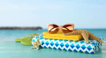 Different beach accessories on table against seaside