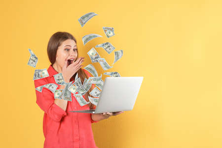 Happy woman with laptop celebrating victory and flying American dollars on color background, space for text