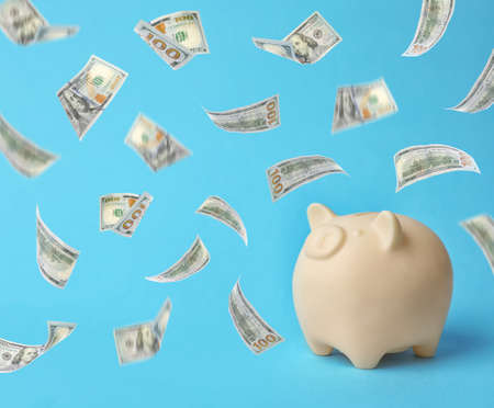 Cute piggy bank and flying American dollars on color background