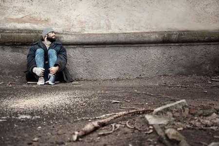 Poor homeless man sitting near wall on street. Space for text