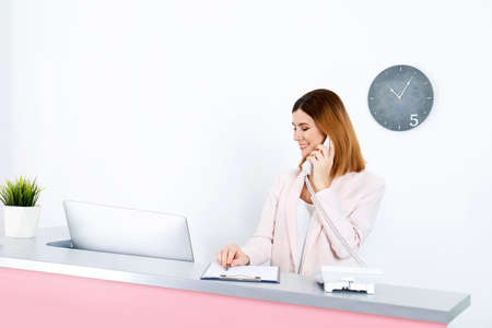 Beautiful woman talking on phone at reception desk in beauty salon. Space for text