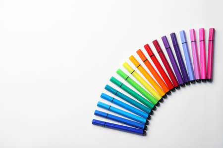 Many colorful markers on white background, top view. Rainbow palette