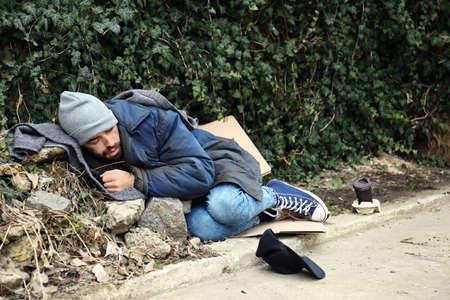 Poor homeless man lying on street in city