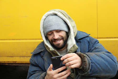 Poor homeless man with stolen smartphone outdoors Stock Photo