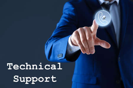 Man pointing at icon on virtual screen against dark background, closeup. Technical support service