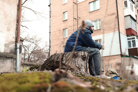 Poor homeless man sitting on stump outdoors Stockfoto