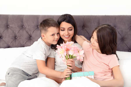 Son and daughter congratulating mom in bed. Happy Mother's Day Standard-Bild