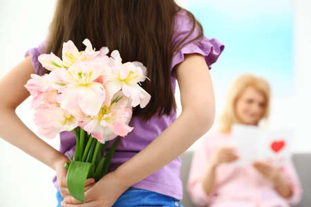 Little daughter congratulating her mature mom at home, closeup. Happy Mother's Day