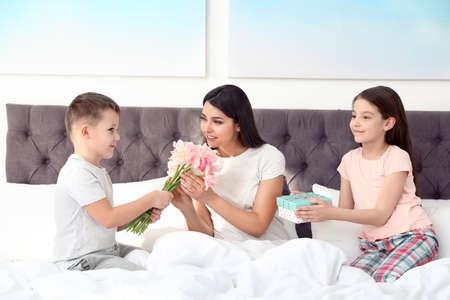 Fils et fille félicitant maman au lit. Bonne fête des mères Banque d'images