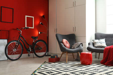Modern living room interior with comfortable armchair, sofa and bicycle