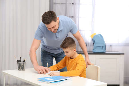 Dad helping his son with homework in room Stock Photo
