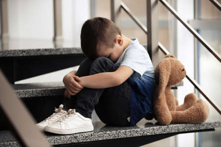 Sad little boy with toy sitting on stairs indoors Stockfoto