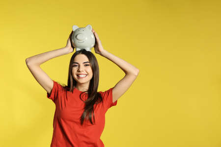 Young woman with piggy bank on color background, space for text. Money saving 免版税图像