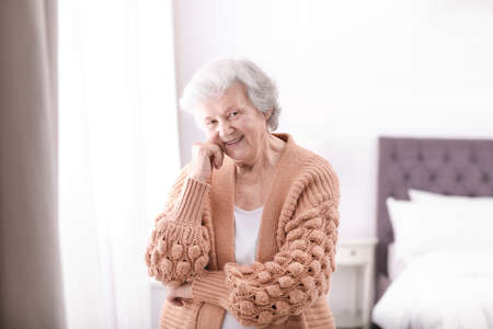 Portrait of beautiful grandmother in sweater at home