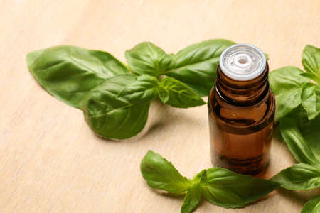 Bottle of basil essential oil and fresh leaves on wooden table. Space for text