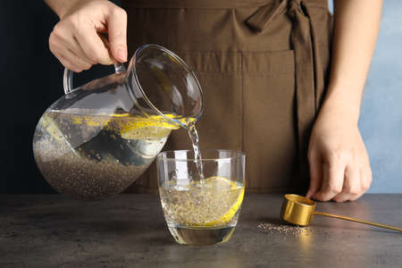 Young woman pouring water with chia seeds and lemon into glass at table, closeup