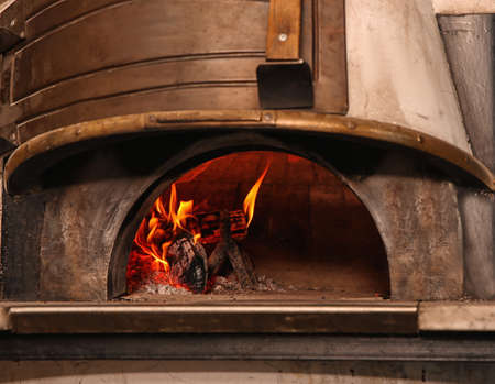 Oven with burning firewood in restaurant kitchen