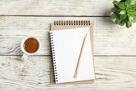 Flat lay composition with notebooks and coffee on wooden background