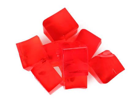 Heap of red jelly cubes on white background, top view