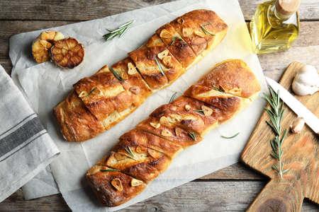 Composición laicos plana con pan de ajo en la mesa Foto de archivo