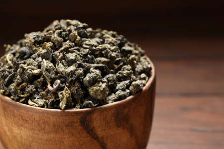 Bowl of Tie Guan Yin oolong tea leaves on wooden background, closeup. Space for text