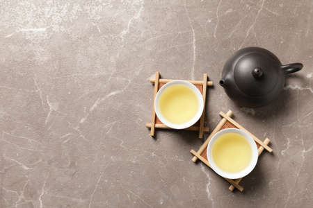 Cups and teapot of Tie Guan Yin oolong on table, top view with space for text