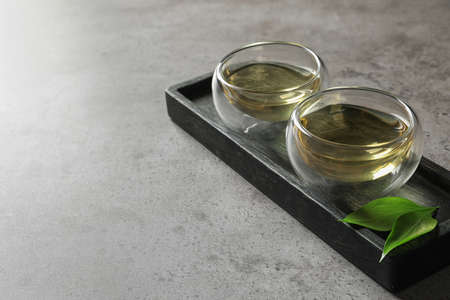 Glass cups of freshly brewed oolong tea on table. Space for text