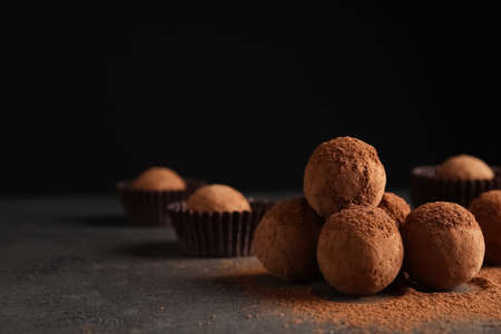 Tasty chocolate truffles powdered with cocoa on table, space for text