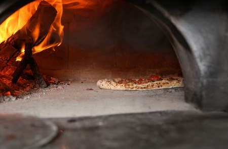 Burning firewood and tasty pizza in oven at restaurant kitchen