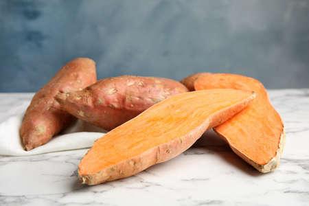 Süßkartoffeln auf Marmortisch vor farbigem Hintergrund Standard-Bild