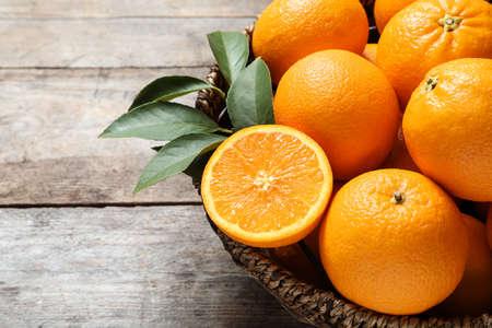 Recipiente de mimbre con naranjas maduras sobre fondo de madera, primer plano. Espacio para texto