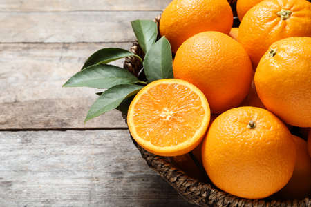 Rieten kom met rijpe sinaasappelen op houten achtergrond, close-up. Ruimte voor tekst