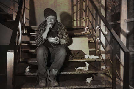 Poor senior man with bowl and bread on stairs indoors