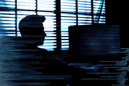 Dark silhouette of cyber criminal hacking computer behind digital symbols