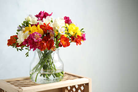 Bouquet of spring freesia flowers in vase on light background. Space for text