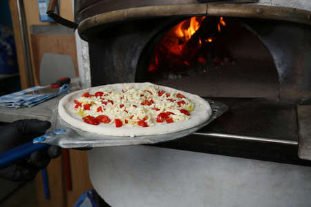 Chef putting tasty pizza into oven in restaurant kitchen Imagens