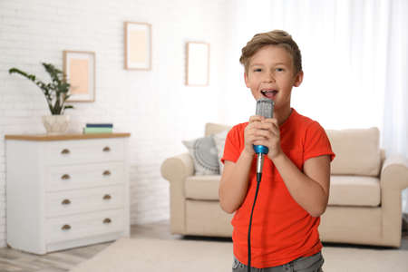 Cute boy singing in microphone at home Imagens
