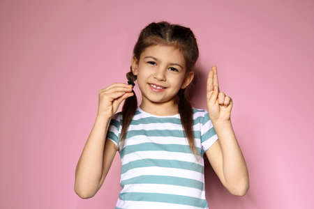 Little girl using sign language on color background